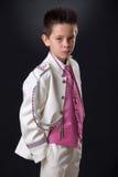 Junge, der ernsthaft in seiner ersten heiligen Kommunion schauend steht Lizenzfreies Stockfoto