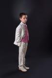 Junge, der ernsthaft in seiner ersten heiligen Kommunion steht Lizenzfreie Stockbilder
