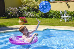 Junge, der Fang im Swimmingpool spielt stockfotos