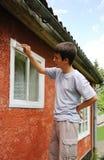 Junge, der Fenster auf der Außenseite befleckt. Lizenzfreie Stockfotografie