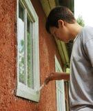 Junge, der Fenster auf der Außenseite befleckt. Lizenzfreies Stockfoto