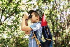 Junge, der Ferngläser im Wald verwendet stockbild