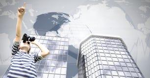Junge, der Ferngläser mit hohen Gebäuden und Weltkarte verwendet Stockbilder