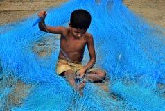 Junge, der Fischernetz repariert Lizenzfreie Stockfotografie