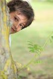 Junge, der flüchtiger Blicken flüchtigen Blick ein Buh spielt lizenzfreie stockbilder