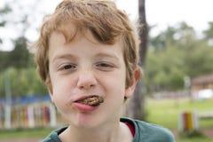 Junge, der Fleischklöschen mit dem Mund voll isst Stockbild