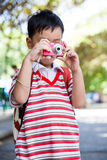Junge, der Foto, auf unscharfem Naturhintergrund macht Aktiver Lebensstil Lizenzfreies Stockfoto