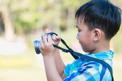 Junge, der Foto durch Kamera, auf unscharfem Naturhintergrund macht aktiv Lizenzfreie Stockfotos