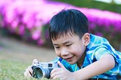 Junge, der Foto durch Kamera, Erforschungsnatur am Park macht Stockbild