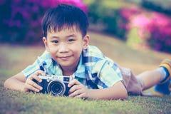 Junge, der Foto durch Kamera, Erforschungsnatur am Park macht aktives lif Lizenzfreie Stockfotos