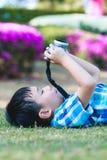 Junge, der Foto durch Kamera, Erforschungsnatur am Park macht aktives lif Lizenzfreies Stockfoto