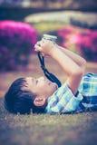 Junge, der Foto durch Kamera, Erforschungsnatur am Park macht aktives lif Stockfoto