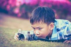 Junge, der Foto durch Kamera, Erforschungsnatur am Park macht Entzückendes c Lizenzfreies Stockbild