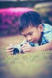 Junge, der Foto durch Kamera, Erforschungsnatur am Park macht Entzückendes c Lizenzfreie Stockfotografie
