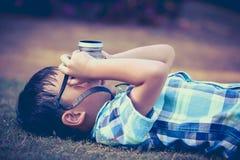 Junge, der Foto durch Kamera, Erforschungsnatur am Park macht Konzepte O Lizenzfreies Stockbild