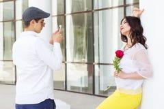 Junge, der Foto seiner hübschen Freundin am Telefon macht Lizenzfreie Stockfotos