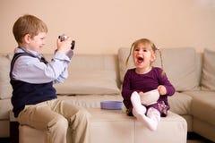 Junge, der Foto seiner Schwester macht Lizenzfreie Stockfotografie