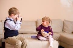 Junge, der Foto seiner Schwester macht Lizenzfreies Stockbild