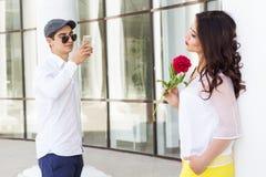 Junge, der Foto seines schönen Mädchens am Telefon macht Stockfoto