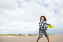 Junge, der Frisbee auf Strand spielt Stockfotos