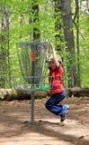 Junge, der Frisbee-Golf spielt Stockfotos