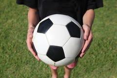 Junge, der Fußball anhält Stockfotografie