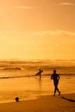 Junge, der Fußball auf Strand spielt Stockfotografie