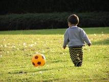 Junge, der Fußball erlernt stockbild