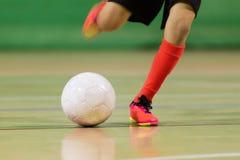 Junge, der Fußballfußball in einer Halle spielt Lizenzfreies Stockbild