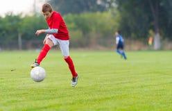 Junge, der Fußballkugel tritt Lizenzfreie Stockbilder