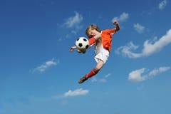 Junge, der Fußball oder Fußball spielt Lizenzfreie Stockfotos