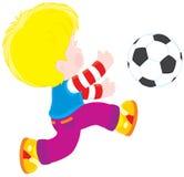 Junge, der Fußball spielt Lizenzfreie Stockfotos