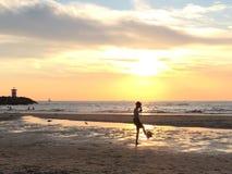 Junge, der Fußball am Strand bei Sonnenuntergang spielt Stockbild