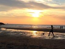 Junge, der Fußball am Strand bei Sonnenuntergang spielt Lizenzfreie Stockfotografie