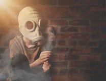 Junge in der Gasmaske, die tote Blume mit Rauche hält stockfotografie