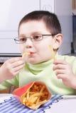 Junge, der gebratene Kartoffel isst Stockfotografie
