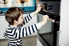 Junge, der gefährlich mit den Griffen auf dem Ofen spielt Stockbild
