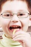 Junge, der geht, gebratene Kartoffel zu essen Stockfotografie