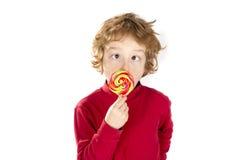 Junge, der gekreuzte Augen lolipop Süßigkeit isst Stockbilder