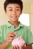 Junge, der Geld in piggybank einsetzt Lizenzfreies Stockbild