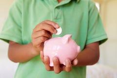 Junge, der Geld in piggybank einsetzt Stockfoto