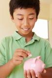 Junge, der Geld in piggybank einsetzt Lizenzfreie Stockfotos