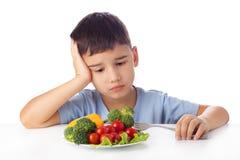 Junge, der Gemüse isst Stockbild