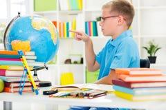 Junge, der Geografie mit Kugel studiert Lizenzfreie Stockfotos