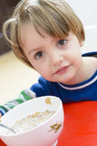 Junge, der Getreide mit Milch isst Stockfoto