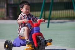 Junge, der glücklich ein Fahrrad reitet stockfotografie