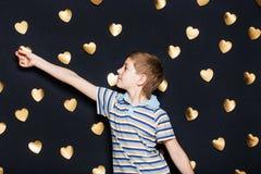 Junge, der Goldherzen auf dunklem strukturiertem Hintergrund befestigt Lizenzfreies Stockbild