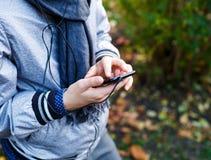 Junge in der grauen Jacke mit grauem Schal hält und benutzt Smartphone mit den Kopfhörern, die über Herbsthintergrund äußer sind  stockfoto