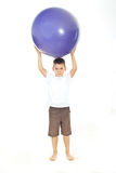 Junge, der große Kugel auf Kopf anhält Lizenzfreie Stockbilder