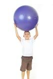 Junge, der große Kugel obenliegend anhält Stockfotografie